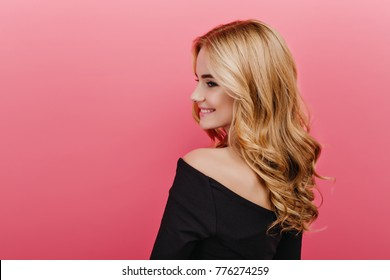 Portrait from back of stylish young woman in black attire. Pleased female caucasian model with blonde curly hairstyle isolated on pink background.