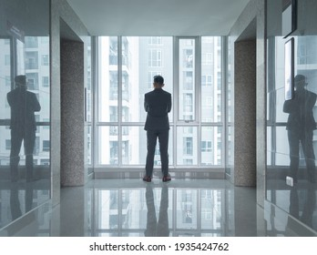 Portrait of back view of young an Asian businessman person walking in front of elevator at corporate office building. People lifestyle.