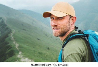 Portrait of backpacker man in baseball cap walking by the foggy cloudy weather mountain range path with backpack. Active sports backpacking healthy lifestyle concept.