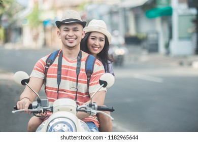 portrait of backpackers couple riding a motorbike to start their journey