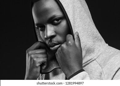 Portrait of bad guy with thug life, weating hoodie, looking at camera. African criminal concept