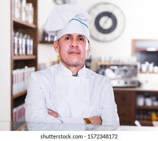 Portrait of baker man is behind the counter in the bakery.