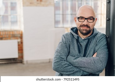 Portrait of a bald bearded middle-aged man wearing gray hooded sweatshirt while looking at camera