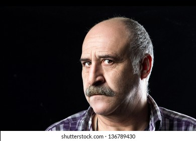 Portrait of bald man with a big mustache expressing uncertainty and fear