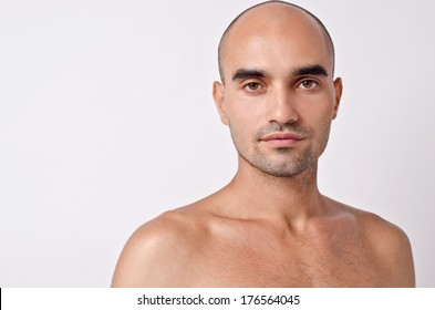 Portrait of a bald man. Bald Caucasian handsome man with topless shoulders. Close up.