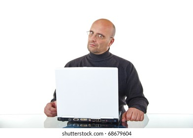 Portrait of a bald man sitting by his laptop working, looking serious and angry