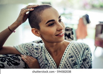 Portrait of a bald woman in a living room in a cozy house in the morning.