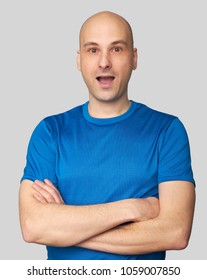 Portrait of bald young amazed man isolated on gray background