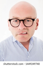 portrait of a bald-headed man with big head making a grimace