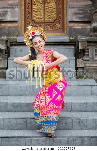Portrait of a Balinese woman dancer holding a Bokor while dancing on the stair