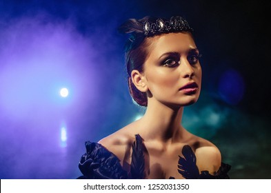 Portrait of ballerina in black dress with diadem and bright makeup. Face of young woman actor under bright light and smoke.