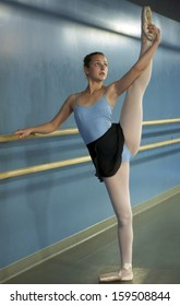 Portrait of a ballerina, in a blue leotard, stretching at the barre