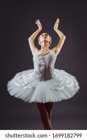 Portrait of the ballerina in the role of a white swan on grey background.  Beautiful, attractive, young, graceful girl professionally performing ballet pas, dressed in a swan costume and pointe shoes