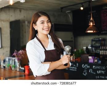 Portrait of Barista preparing coffee with machine at coffee shop.