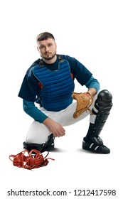 Portrait of a baseball catcher, isolated on white. Pretty man dressed in a uniform and sitting on a knee.