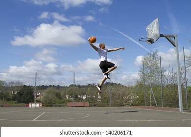 Portrait of a Basketball player in mid air about to Slam Dunk