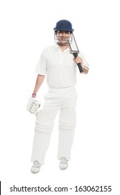 Portrait of a batsman standing with holding a cricket bat and smiling