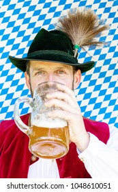 portrait of bavarian man drinking beer on blue and white background