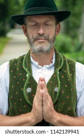 portrait of bavarian man standing outdoors and praying