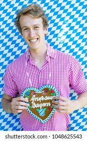 portrait of bavarian young man holding a heart-shaped gingerbread and blue white background