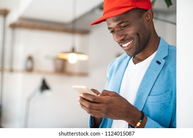 Portrait of beaming african male typing in phone while locating in room. Cheerful entrepreneur during job concept. Copy space