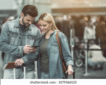 Portrait of beaming bearded male and outgoing girl looking at cellphone in airport. Glad couple concept