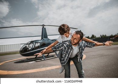 Portrait of beaming bearded man having fun with laughing little boy. He keeping him on back during game on air-stop. They situating opposite rotor plane