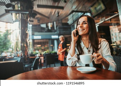 Portrait of beaming girl speaking on mobile while situating at table. She drinking cup of delicious beverage during relax indoor