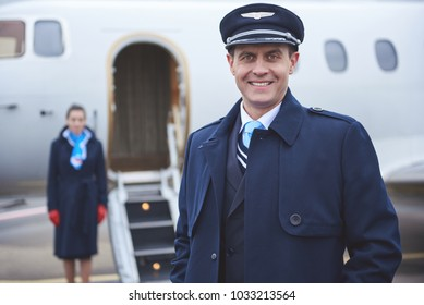 Portrait of beaming pilot looking at camera while situating opposite plane. Labor concept