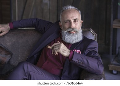 Portrait of beaming unshaven pensioner smoking cigar while sitting on cozy couch in apartment. Luxury concept