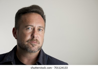 Portrait of a bearded adult man over a gray background with copy space