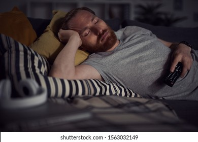 Portrait of bearded adult man sleeping on sofa while watching TV at night, copy space