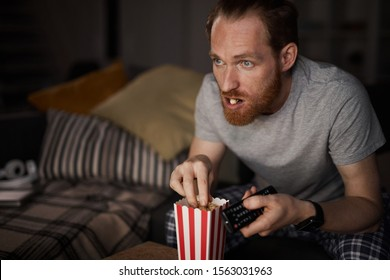 Portrait of bearded adult man watching TV in dark and eating pop corn while enjoying late night movies, copy space