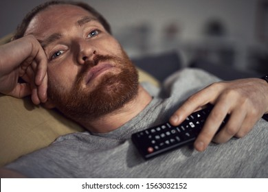 Portrait of bearded adult man watching TV at night while lying on couh in dark room and switching channels, copy space