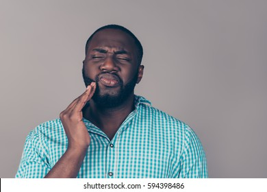 Portrait of bearded   afroamerican man touch cheek. He have strong tooth ache