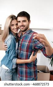 Portrait of bearded boyfriend hugging his girlfriend with keys in new home