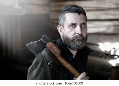 portrait of a bearded brunette man with blue eyes and gray hair  with an ax in his hands in a wooden log hut