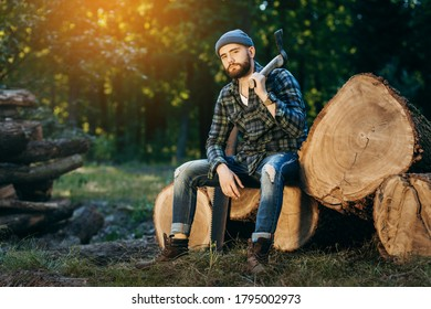 Portrait of a bearded brutal woodcutter holding ax in hand