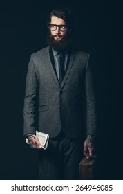 Portrait of a Bearded Businessman in an Elegant Formal Suit Holding a Briefcase and Folded Newspaper While Looking to the Left of the Frame. Isolated on Black.