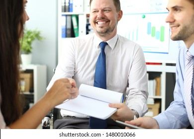 Portrait of bearded businessman sitting in conference room and looking at female manager with gladness. Witty male holding paper folder. Biz meeting concept. Blurred background