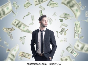 Portrait of a bearded businessman standing with his hands in the pockets near a gray wall under a dollar rain