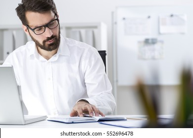 Portrait of a bearded businessman wearing glasses and a white shirt who is checking details of his upcoming meeting in his notebook and typing.