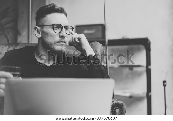 Portrait bearded businessman working on modern loft office. Man sitting in vintage chair, holding glass water. Using contemporary notebook. Black and white. Horizontal, film effect.