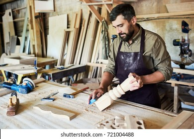 Portrait of bearded carpenter carving beautiful  wooden post in modern workshop, copy space
