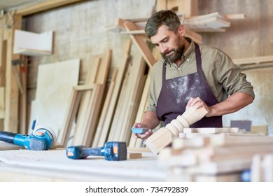 Portrait of bearded carpenter carving intricate  wooden post in modern workshop, copy space