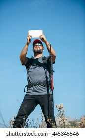 Portrait of bearded climber with backpack taking photo with tablet against of blue sky