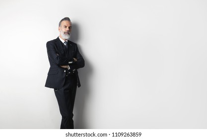 Portrait of bearded confident gentleman wearing trendy suit standing over empty white background. Copy Paste text space