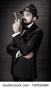 portrait of bearded  gentleman in a suit with unlit cigar in his hand