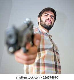 Portrait of a bearded gunman holding the trigger in his hand