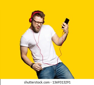 Portrait of bearded guy enjoying metal song and imagining playing bass guitar. Model posing and dancing in studio. Male wearing red headphones and casual clothes